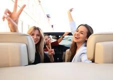 Tre flickor som kör i en konvertibel bil och har gyckel fotografering för bildbyråer