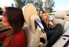 Tre flickor som kör i en konvertibel bil och har gyckel royaltyfria foton