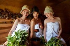 Tre flickor som kopplar av i bastu royaltyfri fotografi