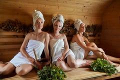 Tre flickor som kopplar av i bastu royaltyfri bild