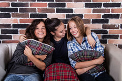 Tre flickor som kramar och ler sammanträde på soffan Arkivbild