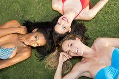 Tre flickor som ligger på deras baksida, på gräset i en parkera  royaltyfri bild