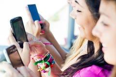 Tre flickor som pratar med deras smartphones Royaltyfri Bild