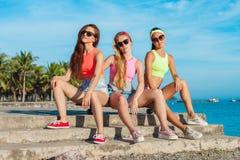 Tre flickor som sitter på longboard på stranden Härlig Seascape Kvinnor i färgglat koppla av för clothers solig sommar Royaltyfria Bilder