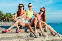 Tre flickor som sitter på longboard på stranden Härlig Seascape Kvinnor i färgglat koppla av för clothers solig sommar Arkivfoto