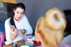 Tre flickor som talar och, sitter i kafé Nätt ung flicka med blac Royaltyfria Bilder