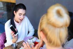 Tre flickor som talar och, sitter i kafé Nätt ung flicka med blac Royaltyfri Fotografi
