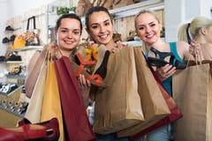 Tre flickor som tillsammans shoppar arkivfoto