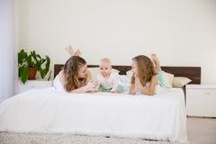 Tre flickor spelar systrar i sovrummet på sängen i morgonen arkivfoton