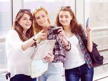 Tre flickor står på flygplatsen och att se minnestavlan En tur med vänner Flickor som gör selfie Royaltyfri Bild