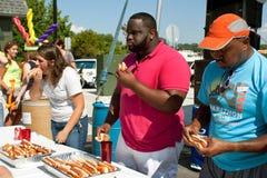 Tre folk konkurrerar i varmkorven som äter strid royaltyfria bilder