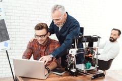 Tre forskare är involverade i inställning - upp och framkallande skrivare 3D En äldre man kontrollerar arbetet av hans lag Arkivbild