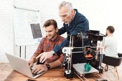 Tre forskare är involverade i inställning - upp och framkallande skrivare 3D En äldre man kontrollerar arbetet av hans lag Arkivbilder