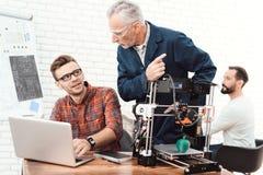 Tre forskare är involverade i inställning - upp och framkallande skrivare 3D En äldre man kontrollerar arbetet av hans lag Arkivfoto