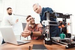 Tre forskare är involverade i inställning - upp och framkallande skrivare 3D En äldre man kontrollerar arbetet av hans lag Arkivfoton