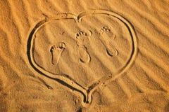 Tre fotspår och hjärta på sand arkivfoton