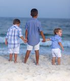 Tre fratelli che si tengono per mano sulla spiaggia fotografia stock