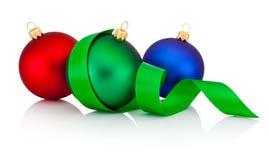 Tre färgade julstruntsaker med bandet som isolerades på vit Royaltyfri Bild