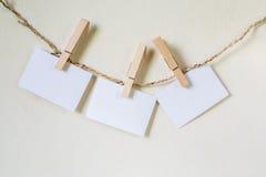 Tre fyrkanter av tomt papper som fixeras till en radtvagninglinje Arkivbilder