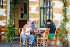 Tre gamala män som sitter på den grekiska tavernaen och spelar brädspel Royaltyfri Bild