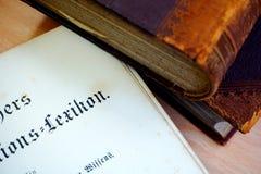 Tre gamla böcker på tabellen och den öppna förstasidan av det gamla lexikonet royaltyfria bilder
