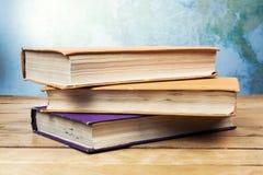 Tre gamla böcker på trätabellen Royaltyfri Foto