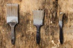 Tre gamla borstar på en yttersida av gammalt och smutsigt Royaltyfri Bild