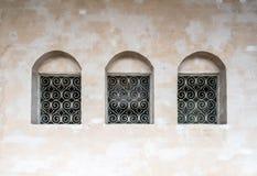 Tre gamla djupa fönster i rad med järngallret arkivfoto