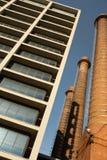 Tre gamla industriella lampglas och en modern byggnad, symboler av forntiden och framtid av staden av Barcelona arkivfoto