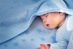 Tre gamla månad behandla som ett barn att sova på den blåa filten Royaltyfri Fotografi