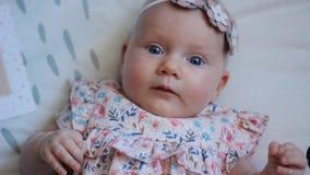 Tre gamla månader behandla som ett barn flickan med blåa ögon Nyfött barn, liten förtjusande fridsam och uppmärksam flicka som se stock video