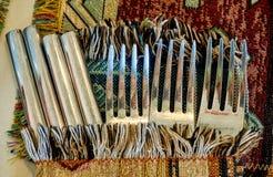 Tre gamla silvergafflar och fyra knivar på tabellen som täckas av den färgrika filten Arkivbilder
