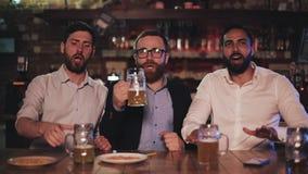 Tre gamla vänner som dricker öl som tillsammans hurrar i en bar Fotbollsfan kamratskap, sportbegrepp stock video