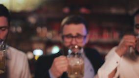 Tre gamla vänner som klirrar deras exponeringsglas med öl i bar Slut upp, ultrarapid Begrepp för berömöljubel stock video