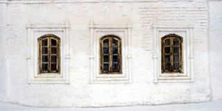 Tre gamla Windows i träramar i en stenvitvägg royaltyfri bild