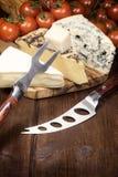 Tre generi di formaggio, di pomodori, di coltello e di forcella Fotografia Stock Libera da Diritti