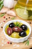 Tre generi di olive in una ciotola con olio d'oliva e le spezie Fotografia Stock