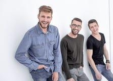 Tre genti che pendono contro la parete, sorridente immagini stock libere da diritti