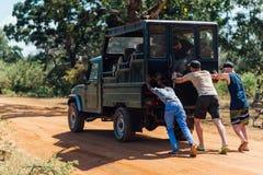 Tre genti che spingono un'automobile che ha attaccato nella sabbia in savana Immagine Stock