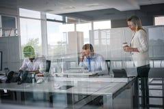 Tre genti di affari che lavorano nell'ufficio Due genti di affari con riferimento a Fotografia Stock