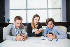 Tre genti di affari del gruppo dei telefoni cellulari e chiacchierata della tenuta Immagine Stock