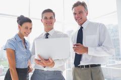 Tre genti di affari sorridenti che tengono un computer portatile Fotografie Stock
