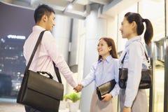 Tre genti di affari sorridenti di handshake fuori dell'ufficio alla notte Immagini Stock