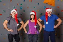 Tre genti di sport in cappelli di Santa che sorridono, tenentesi per mano sulla vita, contro la parete per scalare Fotografie Stock