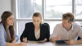 Tre genti si siedono alla tavola bianca in ufficio e discutono il piano di costruzione stock footage