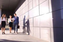 Tre genti sicure di sé, gli studenti, due ragazze ed il tipo vanno e Fotografia Stock Libera da Diritti