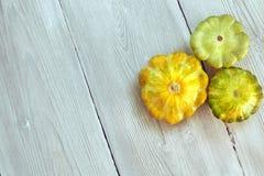 Tre gialli e zucche verdi del cespuglio su fondo di legno bianco Giardino, agricoltura e concetto di azienda agricola Immagine Stock Libera da Diritti