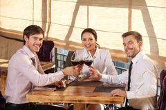 Tre giovani amici che mangiano vino insieme in caffè Fotografia Stock Libera da Diritti