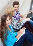 Tre giovani amici che si siedono insieme Fotografia Stock Libera da Diritti
