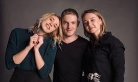 Tre giovani amici che stanno insieme, abbraccianti, ridenti e sorridenti Lo studio sparato nella parete grigia Fotografie Stock